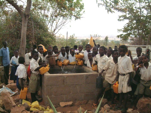 Children from Ving'hawe Primary School bring their 5ltr contributions of Water